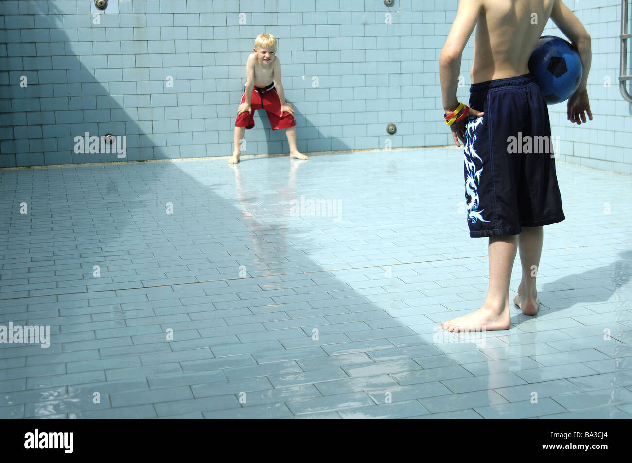 Pool empty children soccer games detail series people boys bath-clothing pools basin-ground tiles ball ball-game - Stock Image