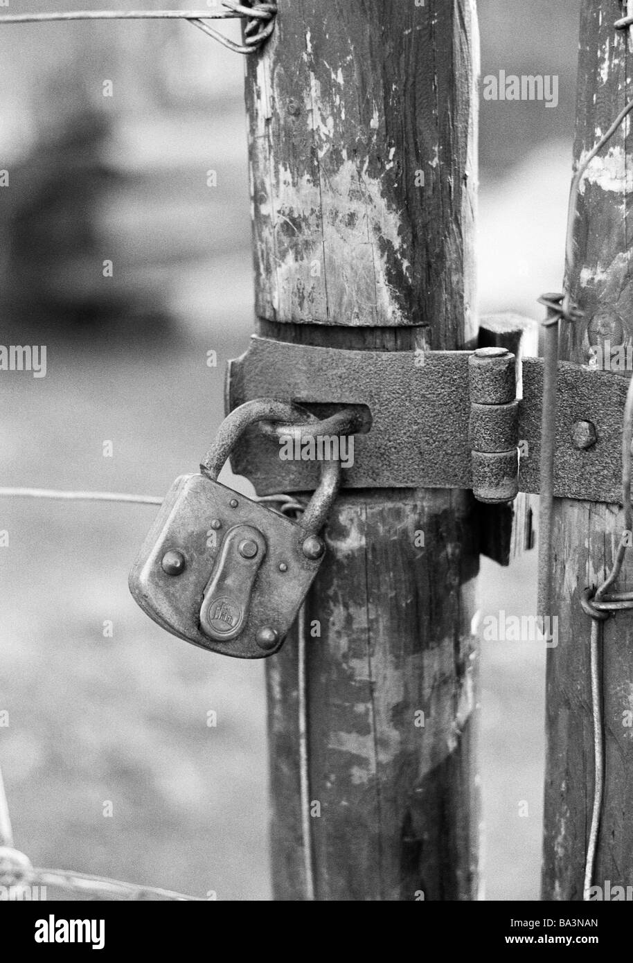 Seventies, black and white photo, symbolic, padlock at a wooden fence, metal fittings Stock Photo