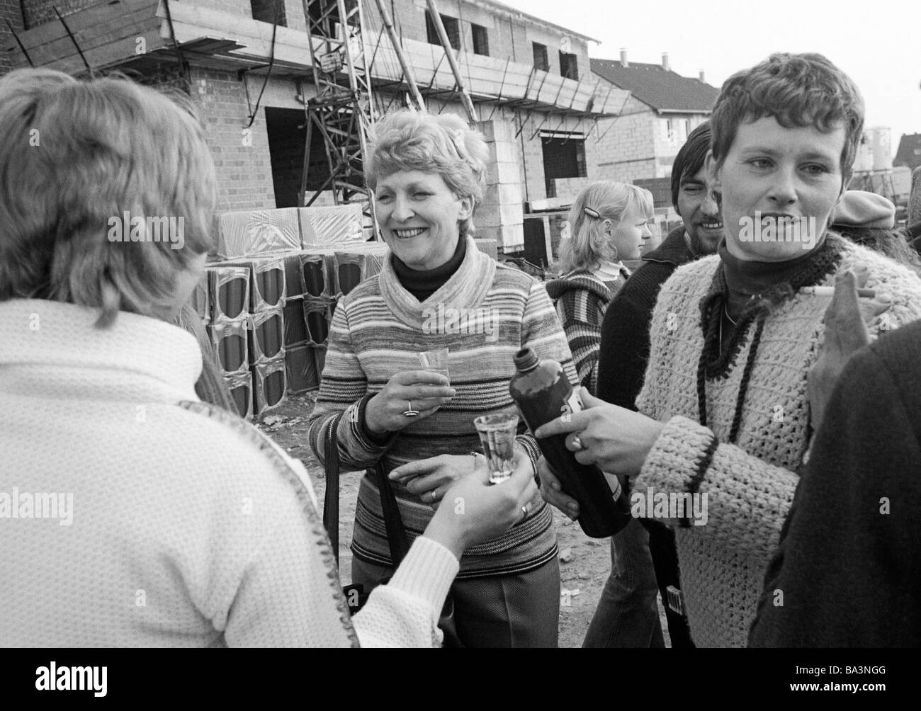 Seventies, black and white photo, building site, shell construction, one-family house, topping out ceremony, proprietoress - Stock Image