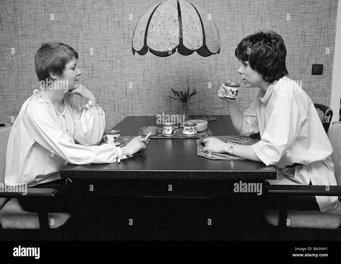 Seventies, black and white photo, people, two young women sitting at the table drinking coffee and smoking a cigarette, - Stock Image