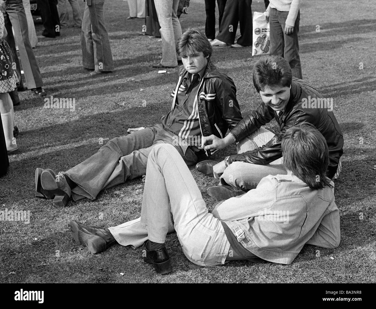 Seventies, black and white photo, people, three teenagers sit on a lawn, two are talking, one looks sad, outsider, - Stock Image