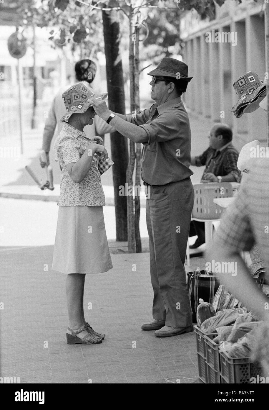 Seventies, black and white photo, holidays, tourism, souvenir shop, older couple, trying on of a hat, man puts on - Stock Image