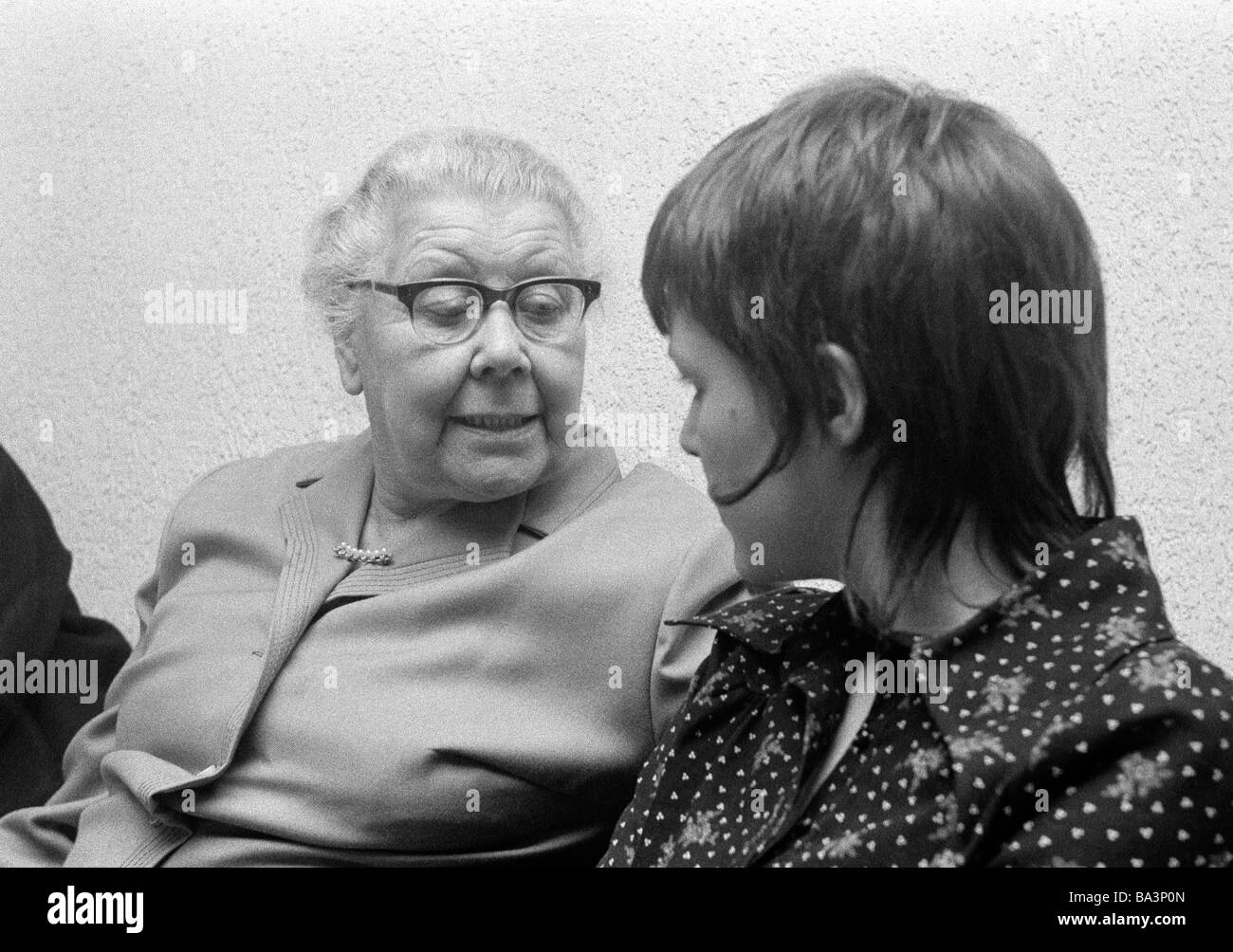 Seventies, black and white photo, people, older woman and young woman talking, aged 70 to 80 years, aged 20 to 25 - Stock Image