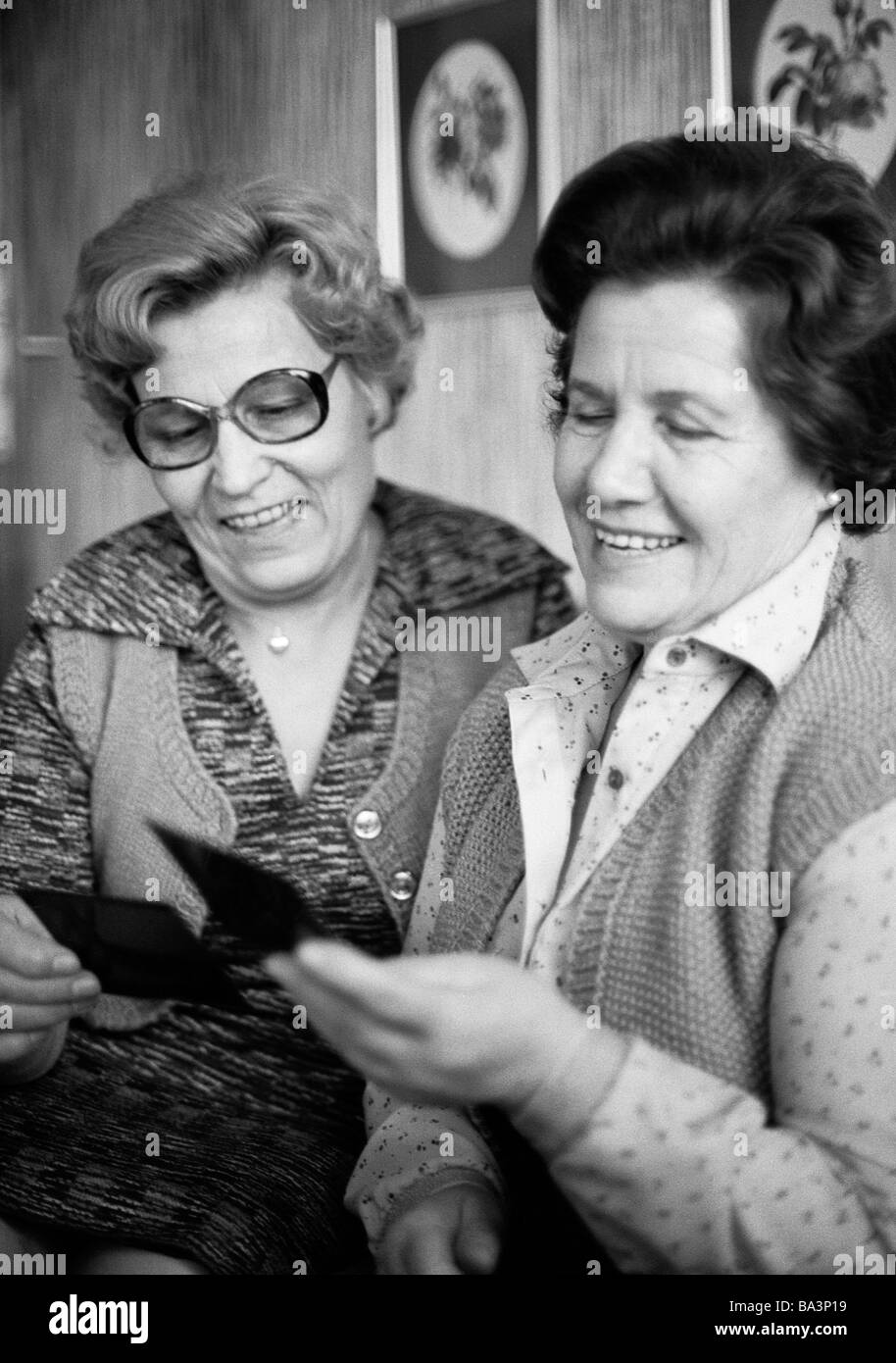 Seventies, black and white photo, people, two older women look at souvenir photos, memories, aged 60 to 70 years, - Stock Image