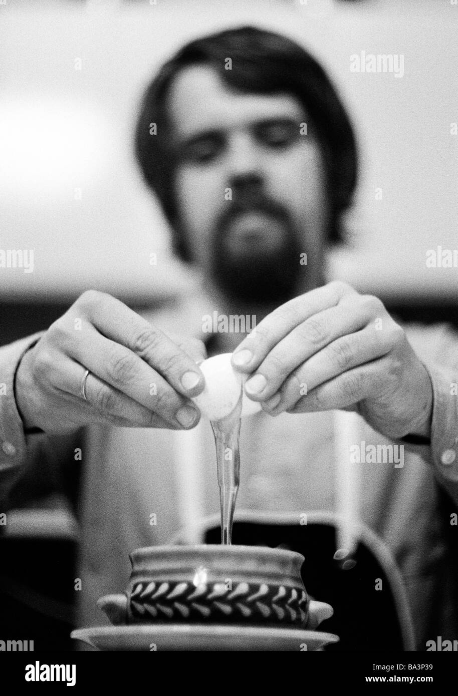 Seventies, black and white photo, people, amateur cook, young man breaks an egg into a bowl, aged 30 to 35 years, - Stock Image