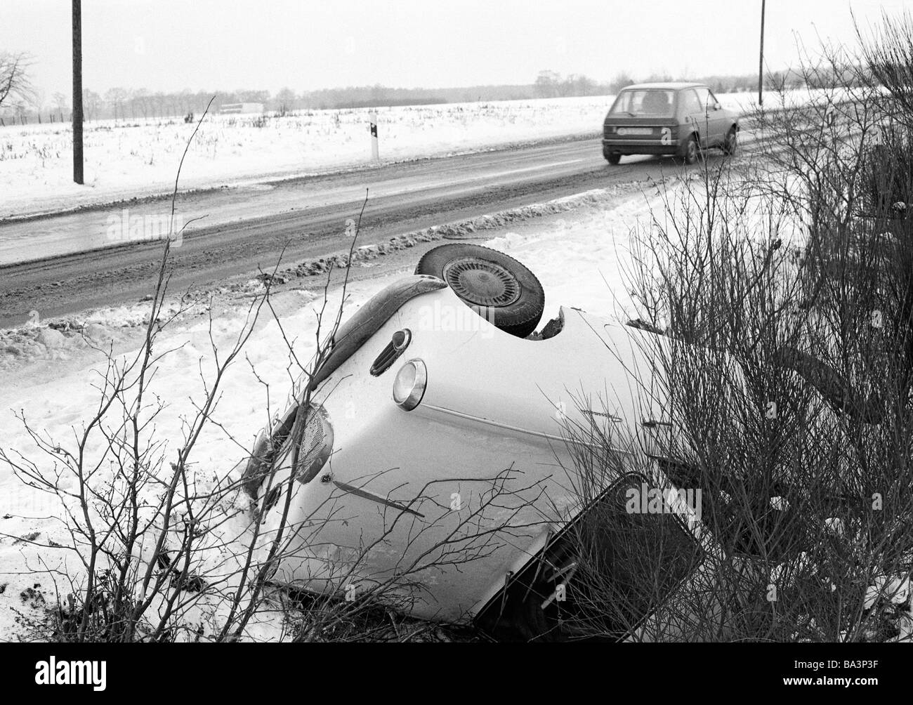 Seventies, black and white photo, traffic, car accident on a country road, passenger car lies in the roadside ditch, - Stock Image