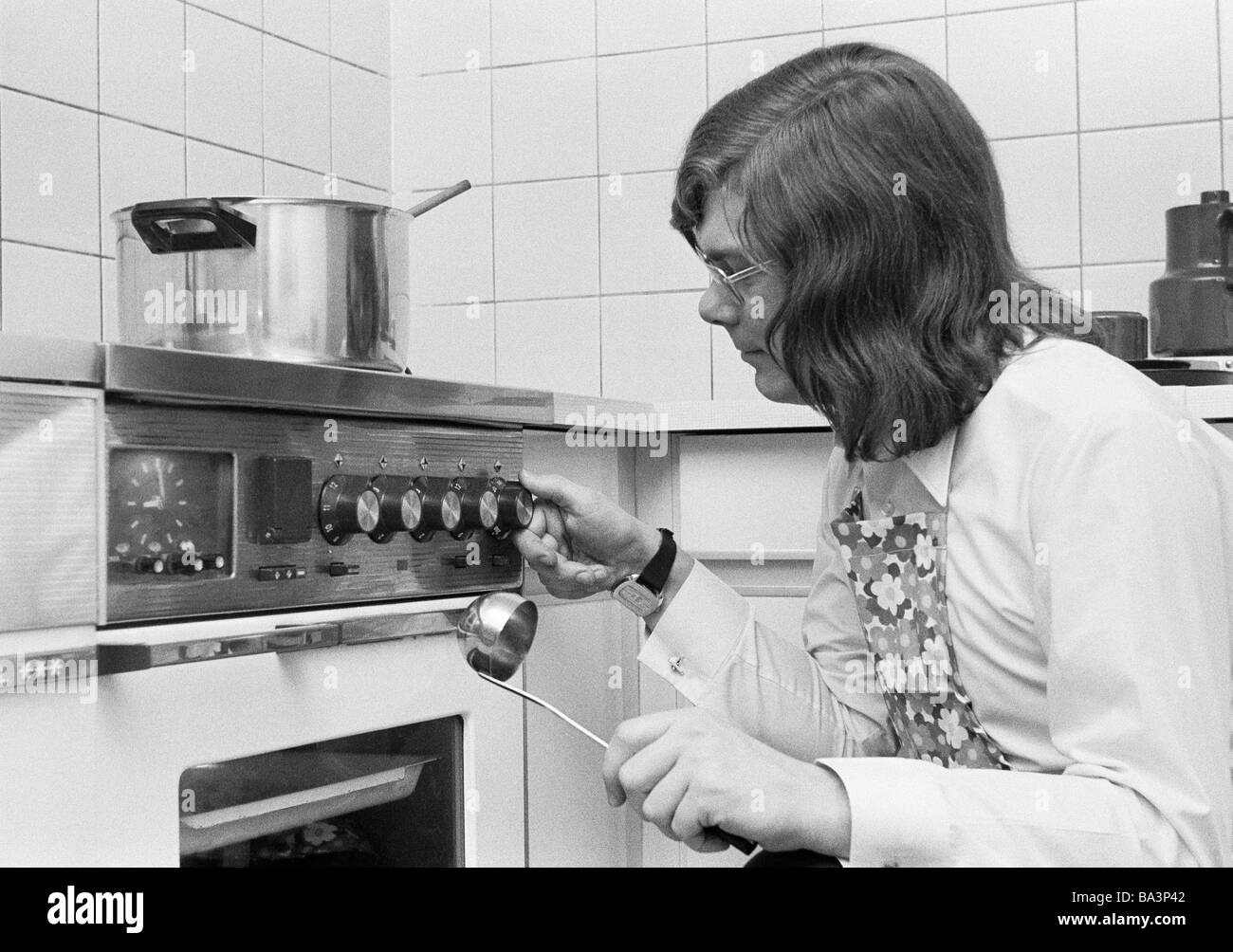Seventies, black and white photo, people, amateur cook, young man crouches with a ladle in front of the cooking - Stock Image