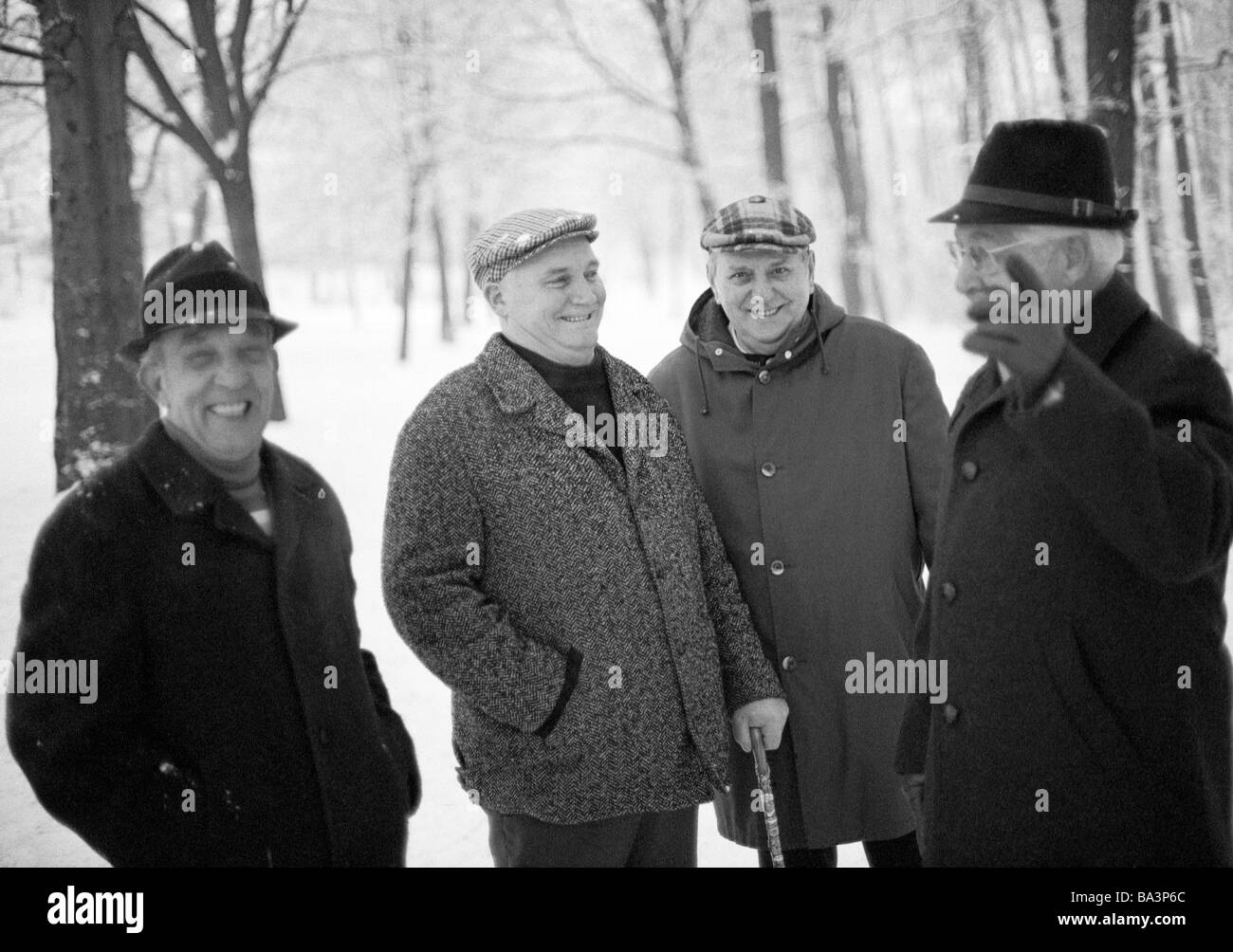 Seventies, black and white photo, people, four older men take a walk, retired persons, winter, snow, walking stick, - Stock Image