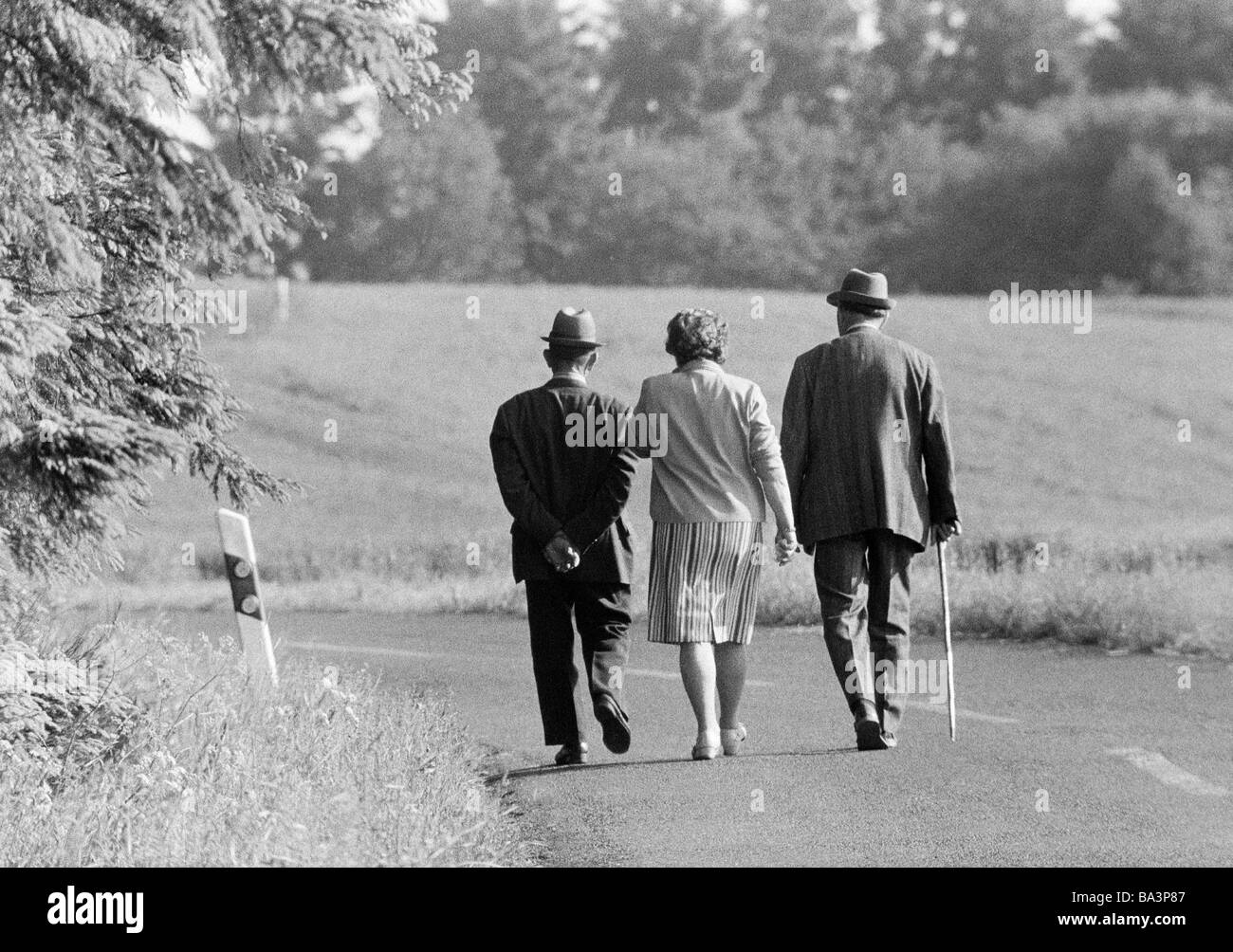 Seventies, black and white photo, people, older people, one older woman and two older men walk along a country road, - Stock Image