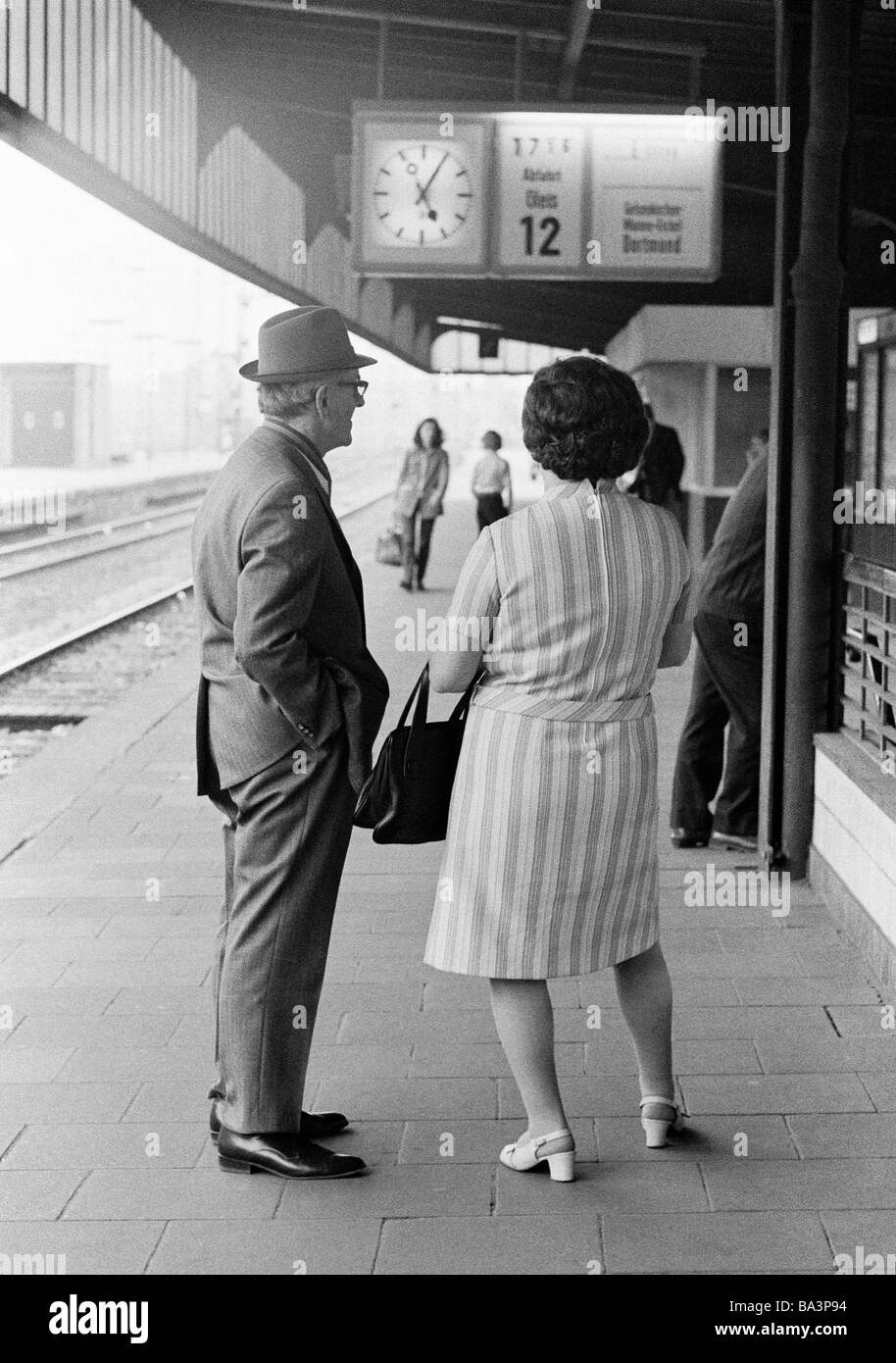 Seventies, black and white photo, people, older couple stands on a platform waiting for the train, railroad station, - Stock Image