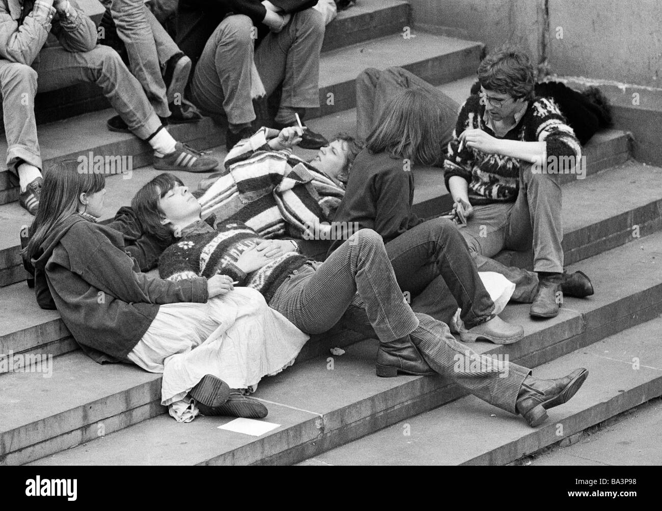 Seventies, black and white photo, people, teenagers sitting on stairs, group of people, leasurewear, long-haired, - Stock Image