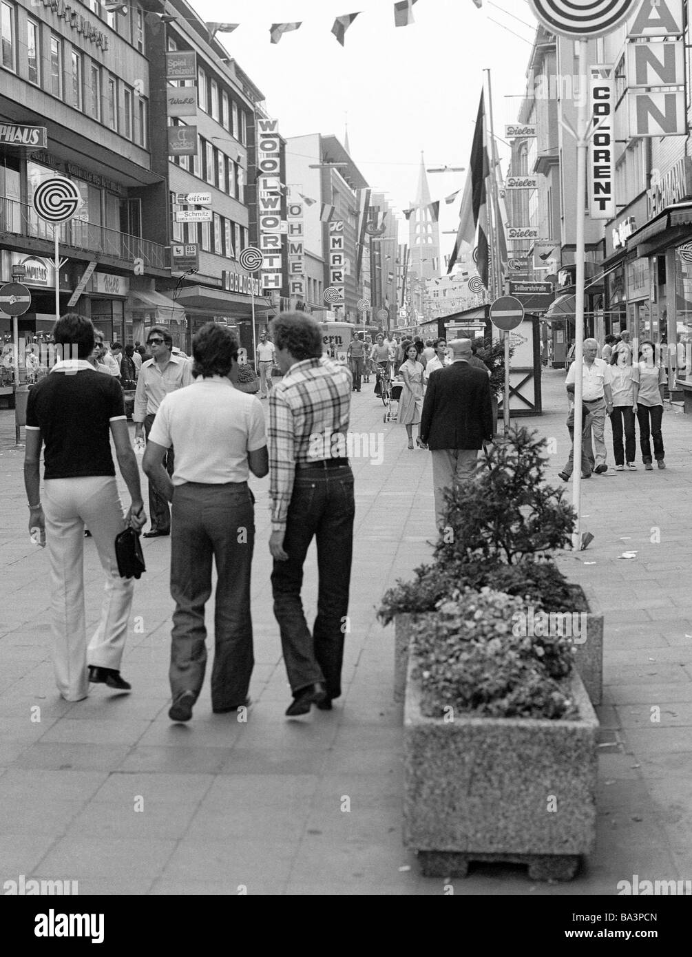 Seventies, black and white photo, people on shopping expedition, three young men, aged 25 to 30 years, shopping - Stock Image