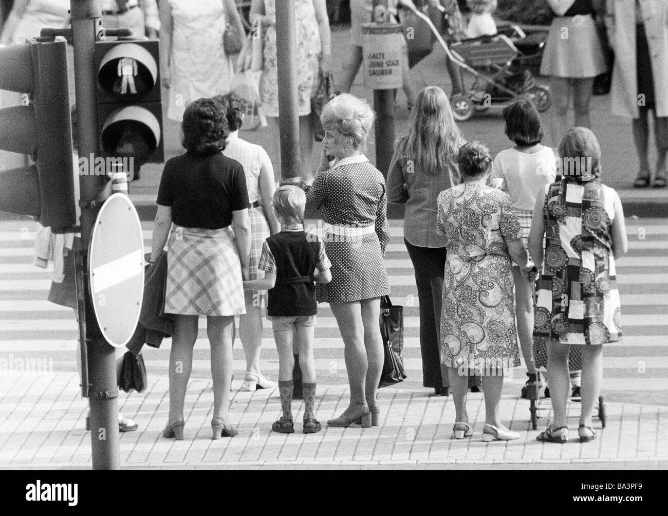 Seventies, black and white photo, people on shopping expedition, several women and a boy waiting at a traffic light, - Stock Image