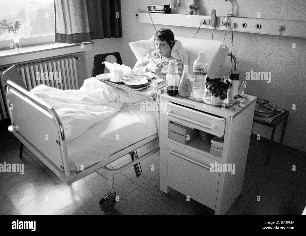 Eighties, black and white photo, people, health, young woman in a hospital, dinner in a sickbed, aged 25 to 30 years, - Stock Image