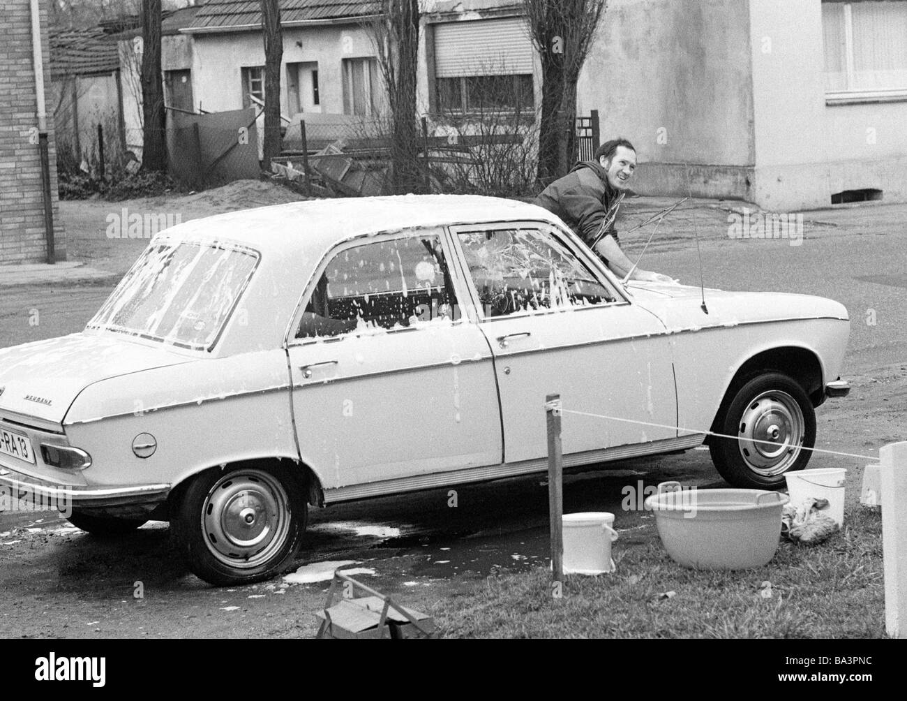 Seventies, black and white photo, young man cleans his car on the roadside by hand, aged 30 to 40 years, Helmut - Stock Image