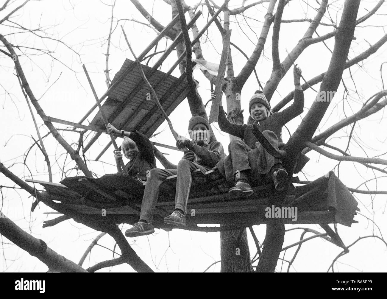 Seventies, black and white photo, people, children, three boys sitting in a tree house, childrens playground, aged - Stock Image