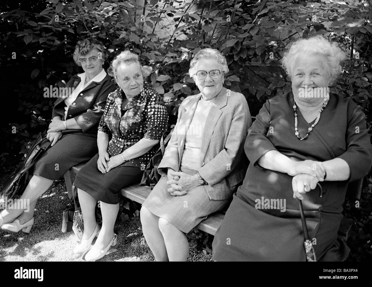 Eighties, black and white photo, people, elder people, four older women sitting on a bench, dress, ladies suit, - Stock Image