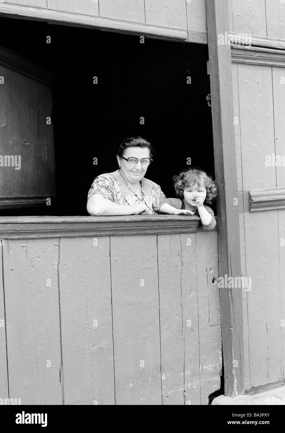 Eighties, black and white photo, people, elder woman and her granddaughter look out of a stable, aged 60 to 70 years, - Stock Image