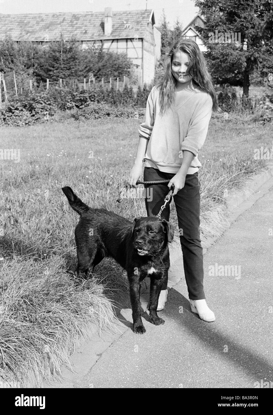 Eighties, black and white photo, human and animal, young girl walks a dog on a lead, aged 14 to 17 years, domestic - Stock Image