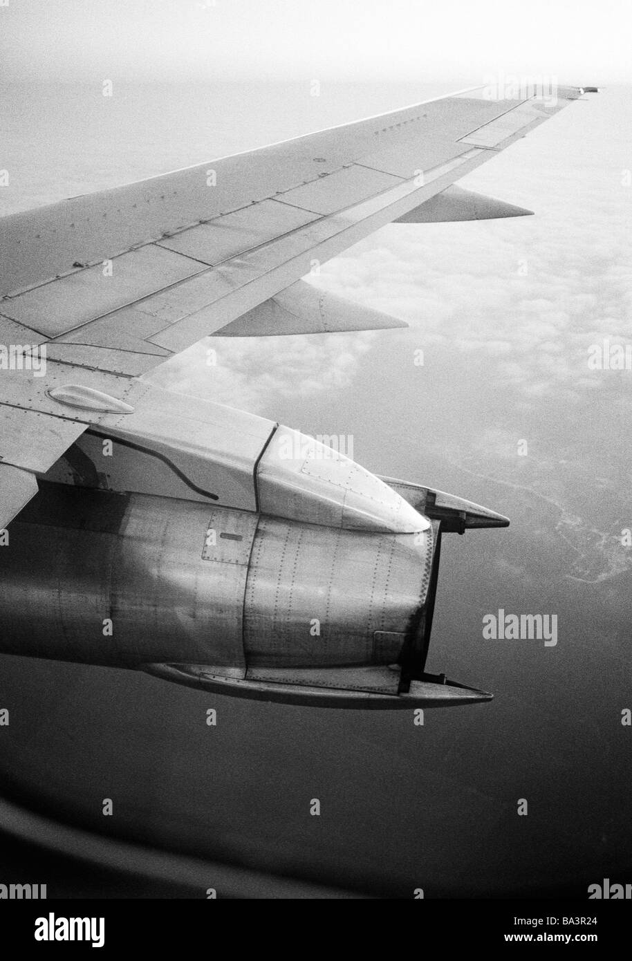 Eighties, black and white photo, travel, holidays, above the clouds, view out of the airplane window to the wing - Stock Image