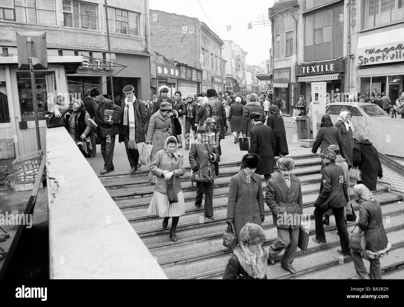 Eighties, black and white photo, people in winter clothes on shopping expedition, shopping street, pedestrian zone, - Stock Image