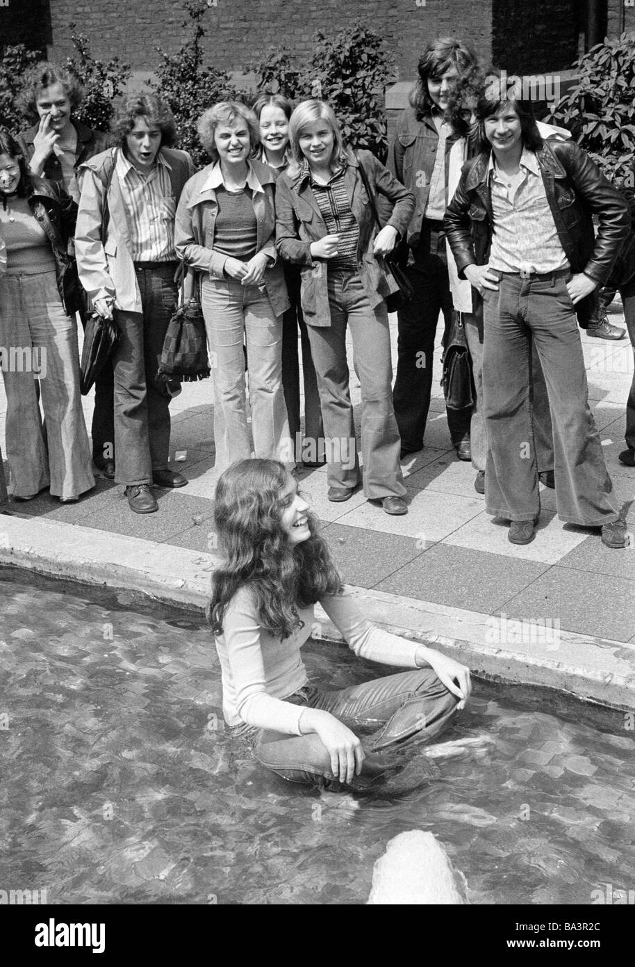 Seventies, black and white photo, humour, people, test of courage, young girl sits fully dressed in a water basin, - Stock Image