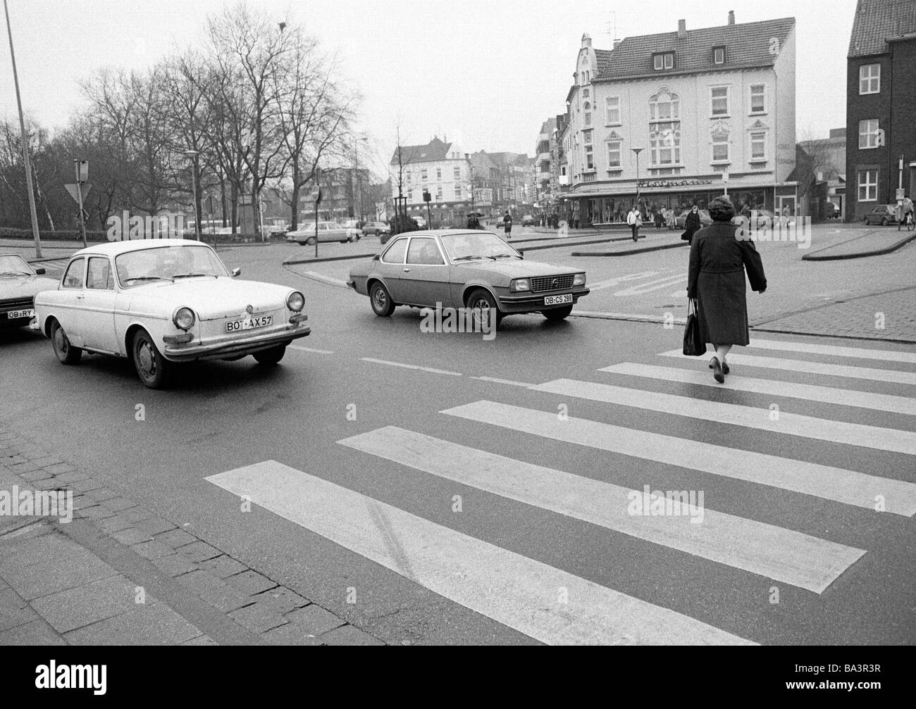 Eighties, black and white photo, road traffic, older woman crosses the road on a cebra crossing, waiting cars, D - Stock Image