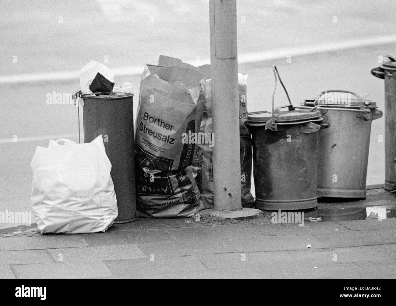 Eighties, black and white photo, dustbins and thrash bags on the roadside - Stock Image