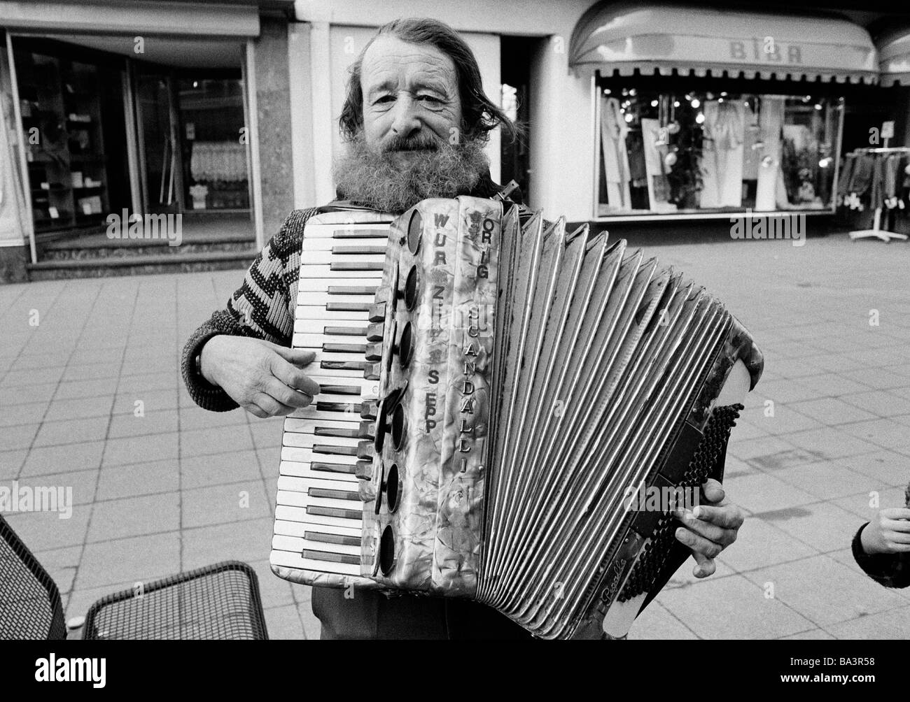 Eighties, black and white photo, people, homeless man stands in a pedestrian zone and plays on a accordion, aged - Stock Image