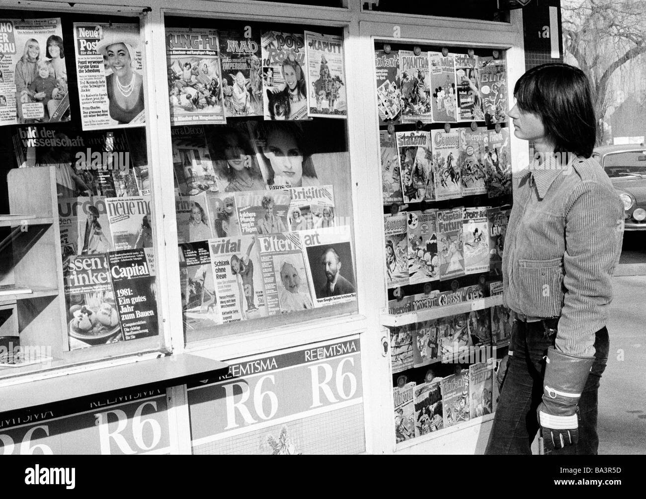 Eighties, black and white photo, people, young boy at a kiosk looking to the magazines, leisurewear, jacket, leather - Stock Image