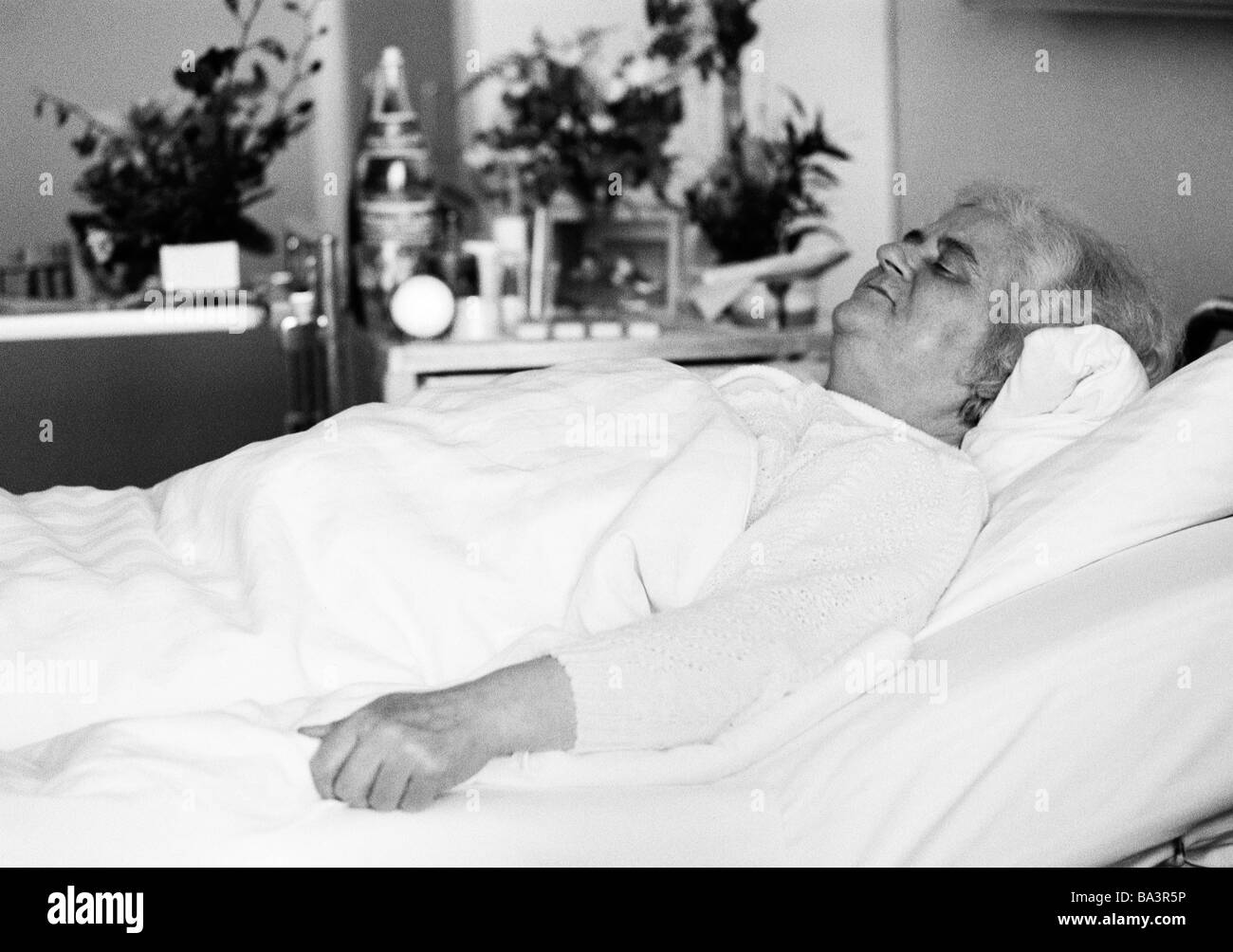 Eighties, black and white photo, people, health, older woman lies in a sickbed of a hospital sleeping, aged 70 to - Stock Image