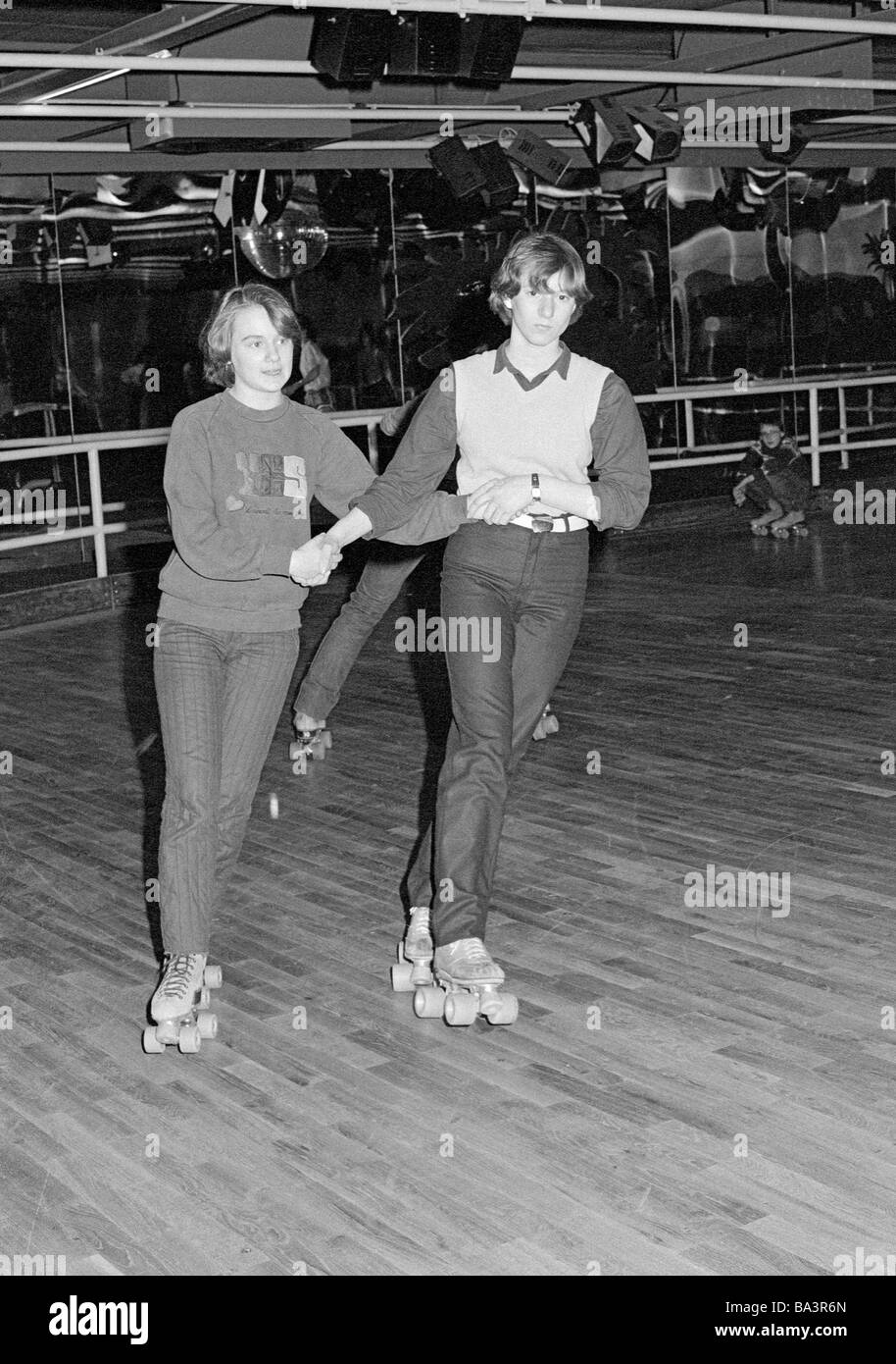 Eighties, black and white photo, people, young couple on rollerblades in a sports hall, trousers, pulli, aged 15 - Stock Image