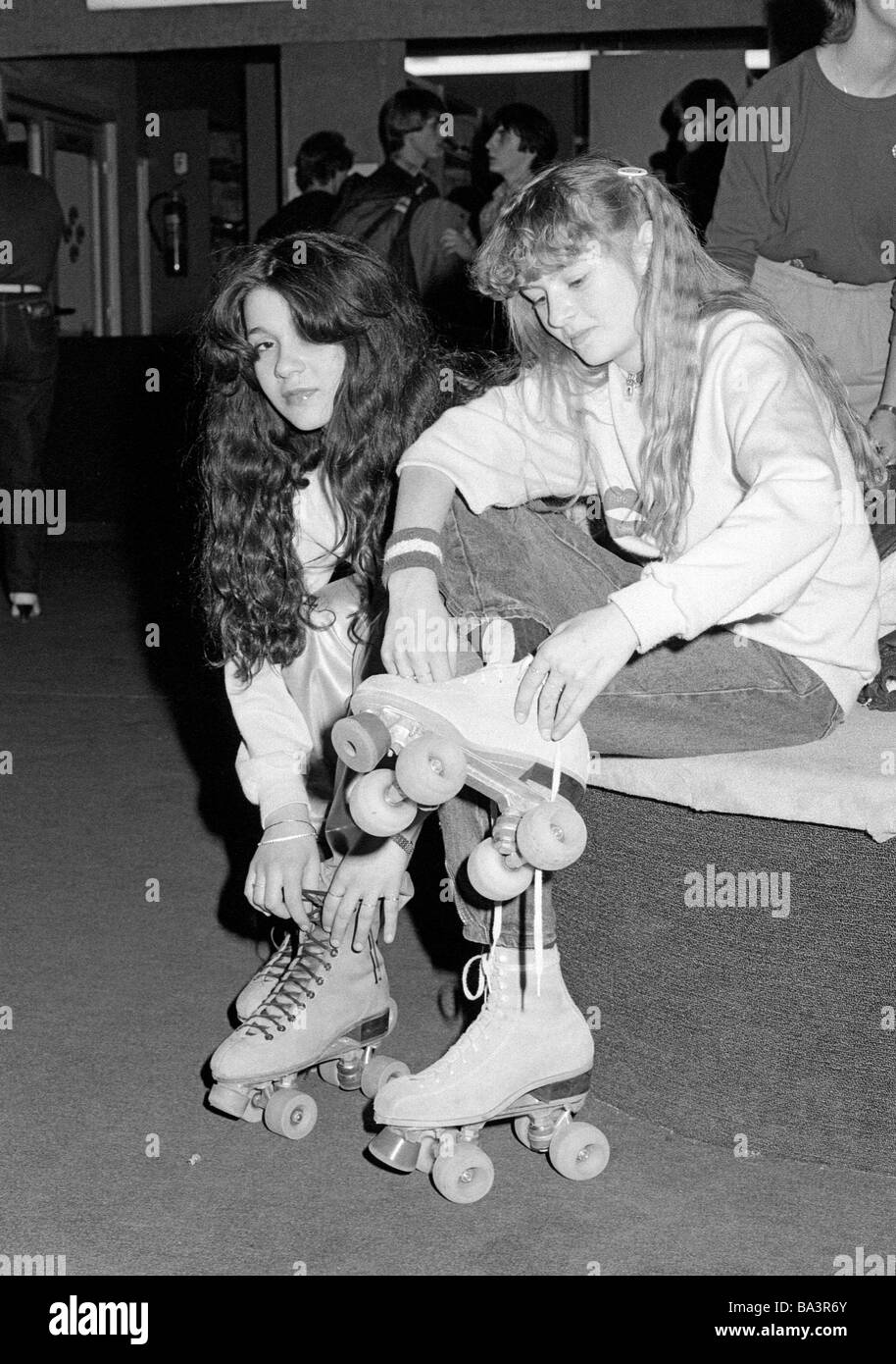 Eighties, black and white photo, people, two young girls sit side by side and put on their rollerblades, jeans trousers, - Stock Image