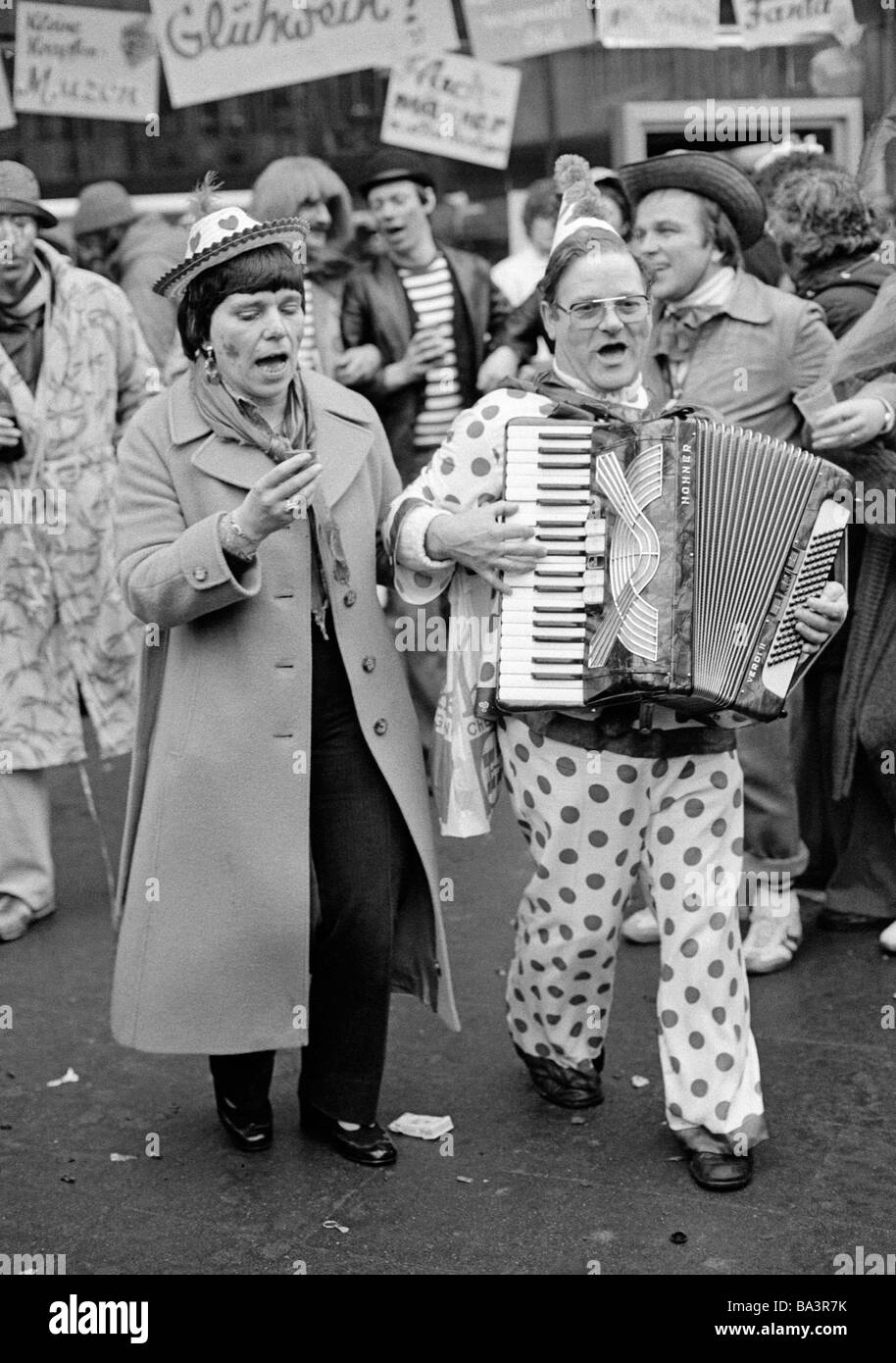 Eighties, black and white photo, people, Rhenish carnival, Rose Monday parade 1981, musician dressed in a clown - Stock Image