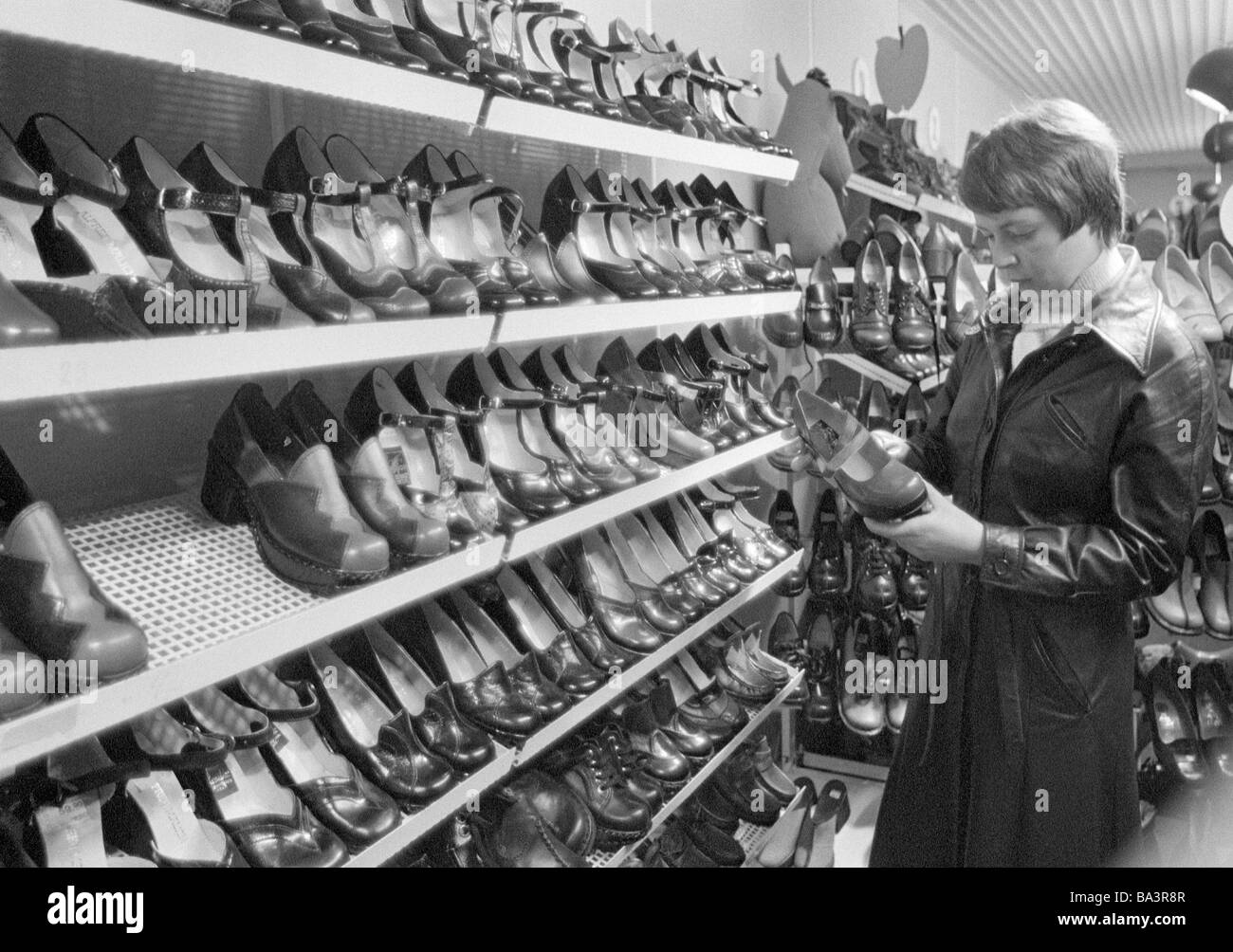 Seventies, black and white photo, economy, retailing, young woman in a footwear store, shelves with shoes, aged - Stock Image