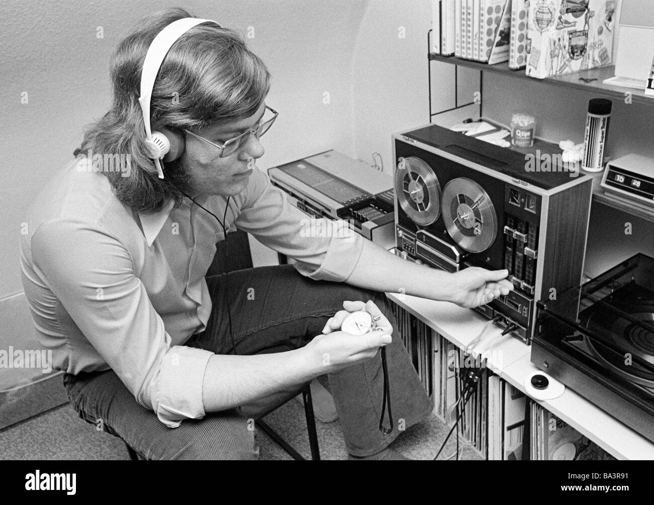 Seventies, black and white photo, people, young man at his tape recorder, earphone, stopwatch in his hand, freetime, - Stock Image