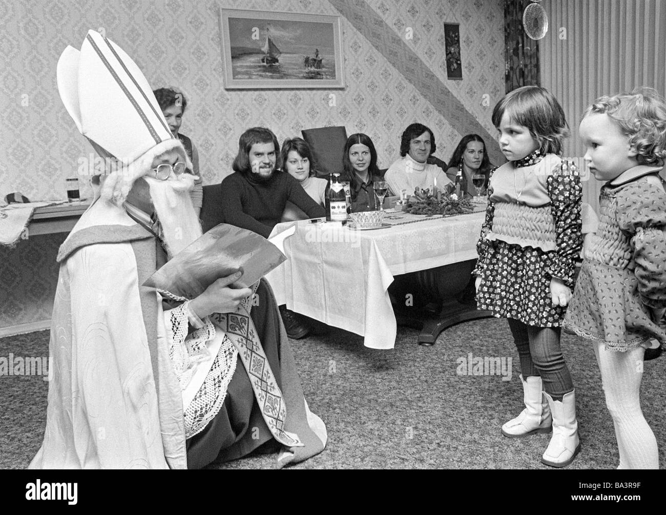 Seventies, black and white photo, Christmas, St. Nicholas Day, Santa Claus visits a family and talks with two little - Stock Image