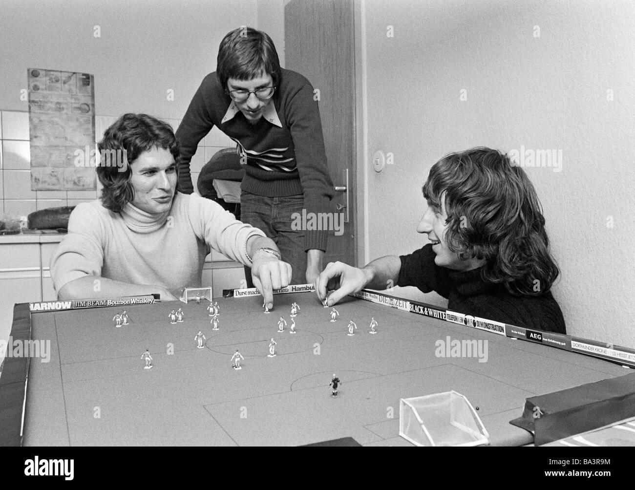 Seventies, black and white photo, people, three young men playing table football, freetime, hobby, long-haired, - Stock Image