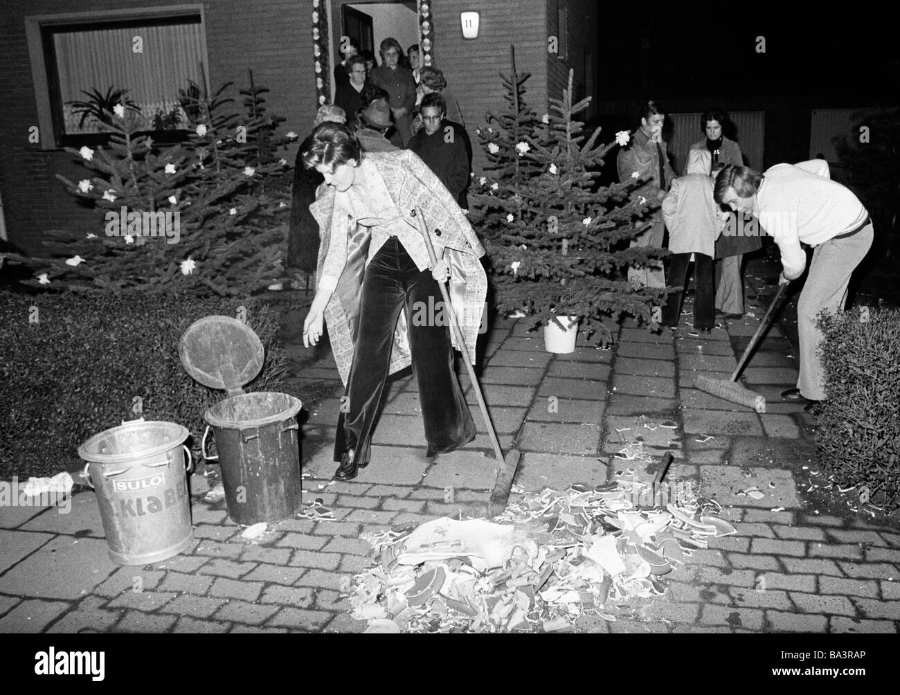Seventies, black and white photo, marriage, eve-of-wedding party, groom and bride sweep up the caramic shards and - Stock Image