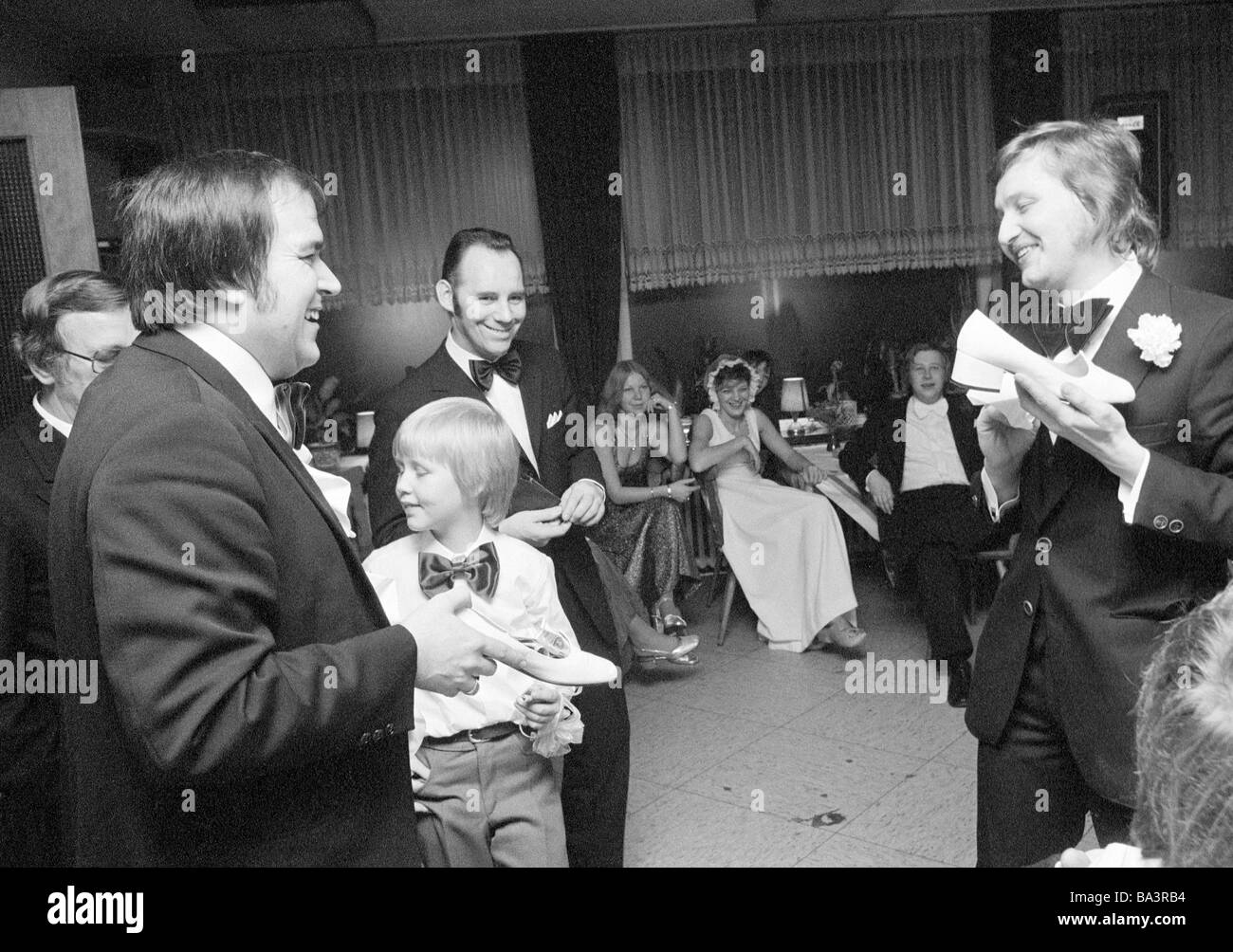 Seventies, black and white photo, people, marriage, bridal shoe auction, two men hold the bridal shoes in the hands - Stock Image