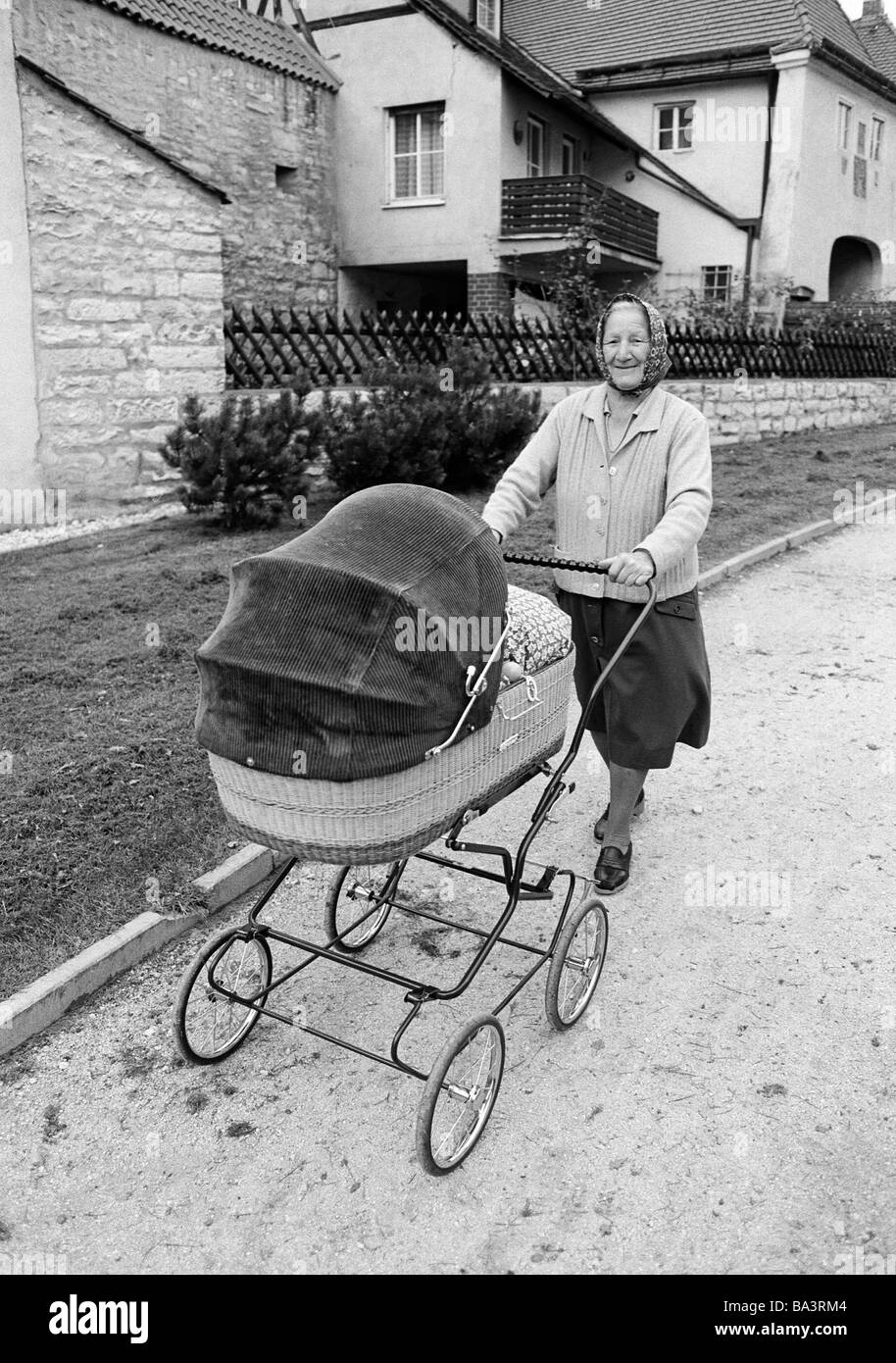 Eighties, black and white photo, people, elder people, older woman walking with a buggy, waistcoat, skirt, kerchief, - Stock Image