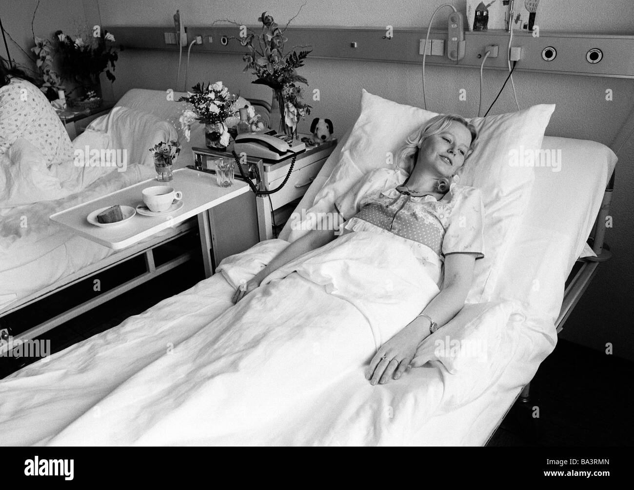 Eighties, black and white photo, people, health, young woman lies in a sickbed of a hospital, aged 30 to 40 years, - Stock Image