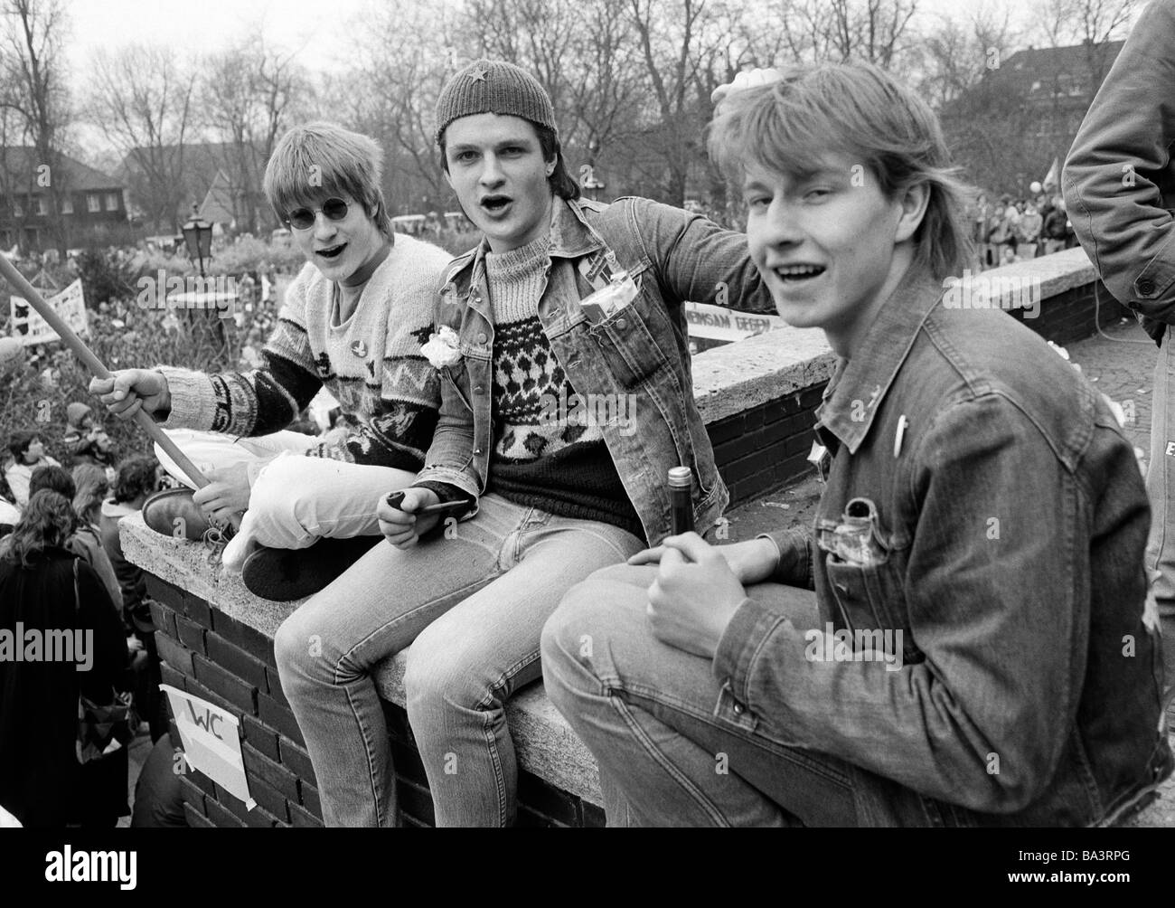 Eighties, black and white photo, people, three teenagers sit on a wall having fun, leisurewear, jeans suit, jeans - Stock Image