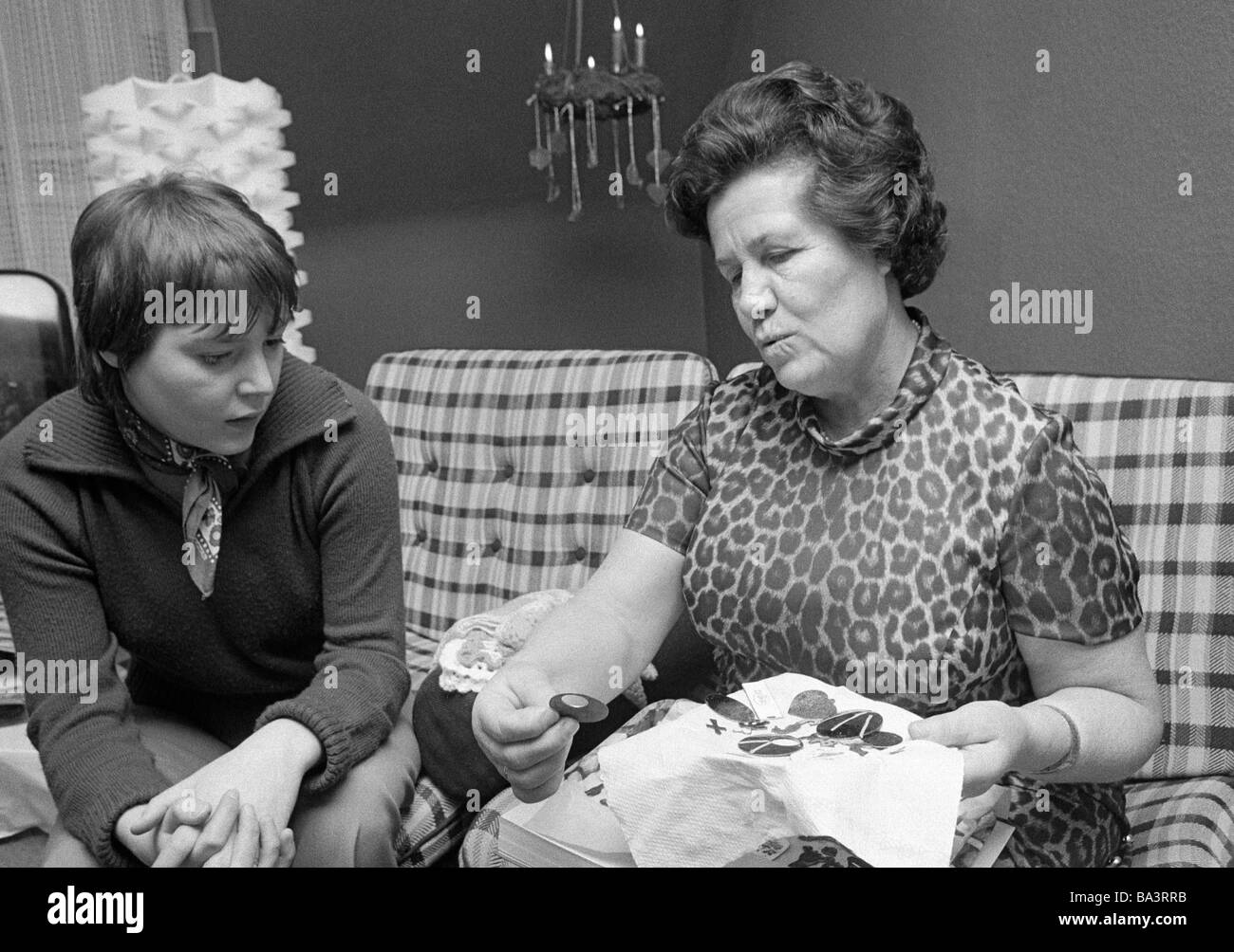 Seventies, black and white photo, people, older woman and young woman sit together in a living room and look at - Stock Image