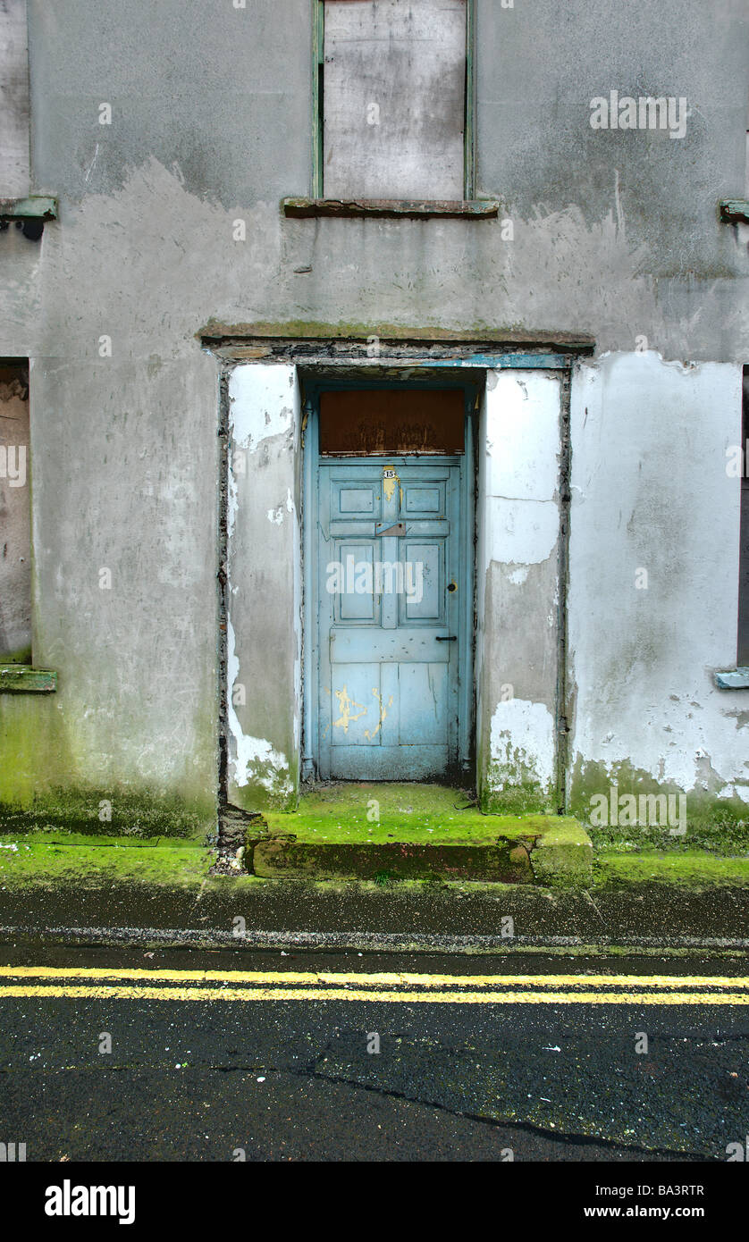 A very run down house doorway with moss on pavement and double yellow lines - Stock Image