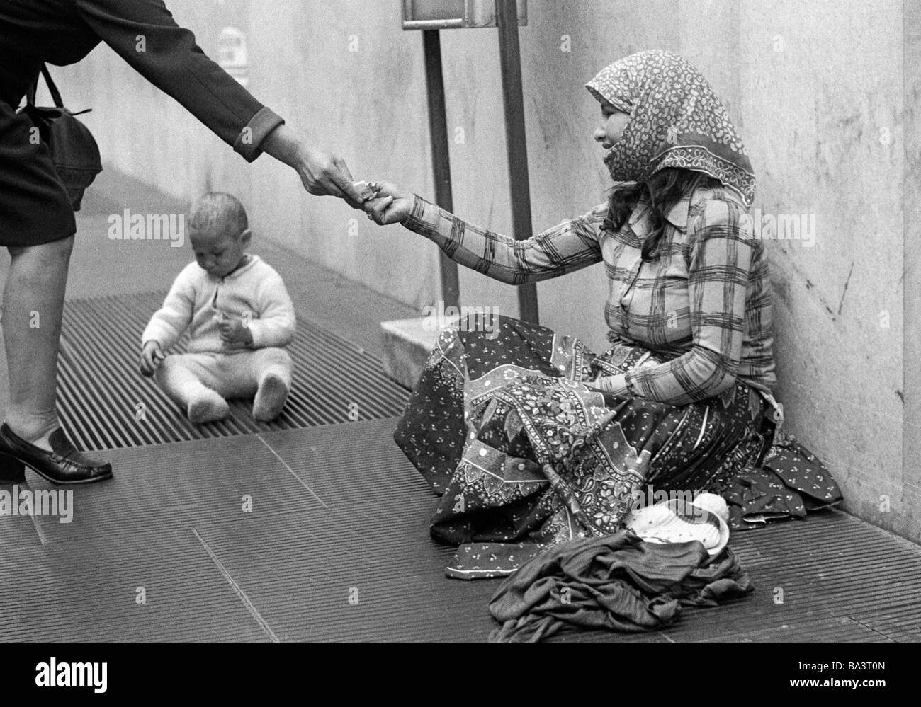 Seventies, black and white photo, people, poorness, beggar-woman sits at the roadside, her baby plays on a grating, - Stock Image
