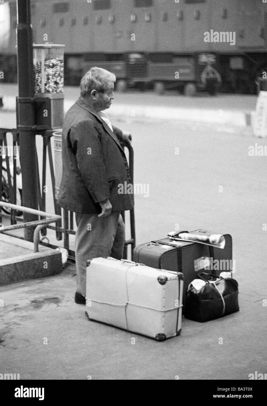 Seventies, black and white photo, people, older man stands on a platform, railroad station, suitcases, luggage, - Stock Image