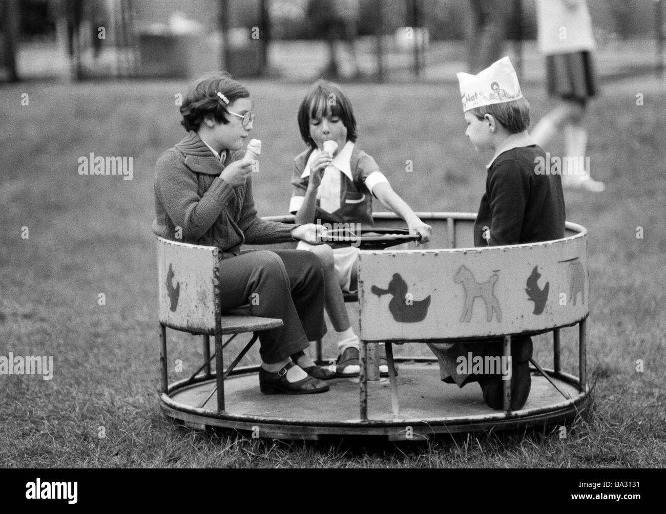 Seventies, black and white photo, people, children, childrens treat, two girls and a boy with a paper cap on his - Stock Image