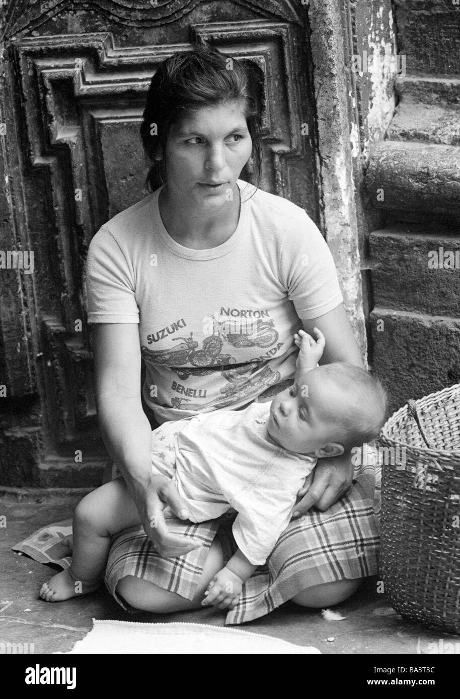 Seventies, black and white photo, people, poorness, beggar-woman sits at the roadside holding her baby in the arms, - Stock Image