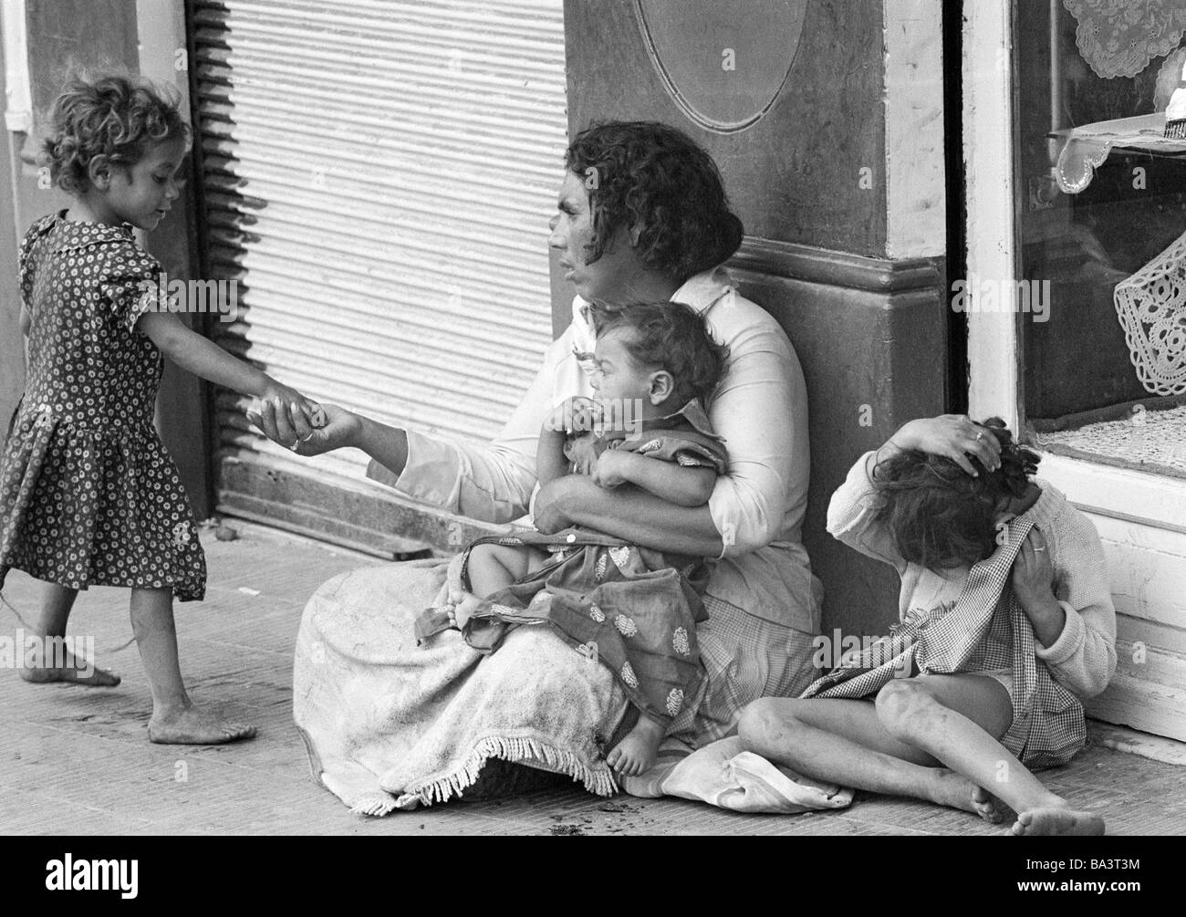 Seventies, black and white photo, people, poorness, beggar-woman sits at the roadside with three children, a girl - Stock Image